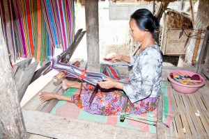 A craftswoman weaving in a traditional Sasak village